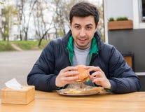 Un retrato de antropófago joven una hamburguesa en café de la comida de la calle Imagen de archivo libre de regalías
