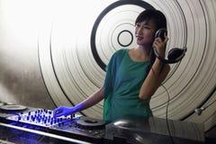 Un retrato de DJ femenino que juega música en un club nocturno Imagen de archivo