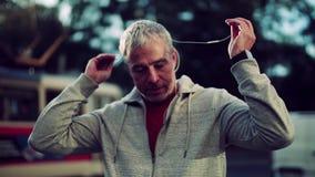 Un retrato de un hombre maduro activo con los auriculares que se colocan al aire libre en ciudad almacen de video
