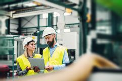 Un retrato de un ingeniero industrial del hombre y de la mujer con la tableta en una fábrica foto de archivo