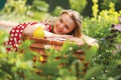 Un retrato de la muchacha está en un jardín del verano Imagen de archivo libre de regalías