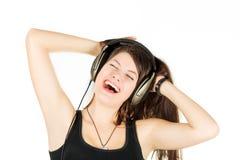 Un retrato de la muchacha está en una ropa de deportes que cante y escuche música en auriculares Foto de archivo