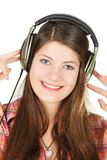 Un retrato de la muchacha sonriente en auriculares, de que las sostiene las manos Fotografía de archivo libre de regalías
