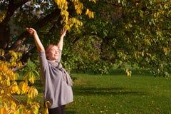 Un retrato de la mujer joven embarazada que goza del parque del otoño con los brazos abiertos El concepto de embarazo y de la arm imagen de archivo libre de regalías