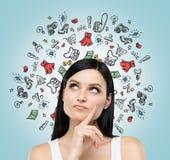 Un retrato de la señora que piensa en compras Los iconos coloridos de las compras están volando en el aire Imagen de archivo libre de regalías
