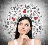 Un retrato de la señora que piensa en compras Los iconos coloridos de las compras se dibujan en el muro de cemento Fotografía de archivo