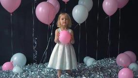 Un retrato de las sonrisas hermosas de una niña y los controles en las manos colorean el globo en el estudio con muchos globos y  almacen de video