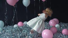 Un retrato de las sonrisas hermosas de una niña y los controles en las manos colorean el globo en el estudio con muchos globos y  almacen de metraje de vídeo