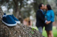 Un retrato de un par de zapatos de bebé con una mujer embarazada y su marido en el fondo fotografía de archivo