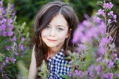 Un retrato de un pelo largo del pequeño girlwith lindo en exterior en la puesta del sol en el campo de flores púrpuras foto de archivo