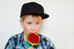 Un retrato de un pequeño muchacho rubio lindo en casquillo negro y camisa comprobada que come una piruleta brillante aislada sobr Fotografía de archivo