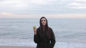 Un retrato de una muchacha feliz hermosa que sostiene y que come una manzana en la costa en un día frío almacen de metraje de vídeo