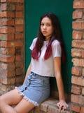 Un retrato de una muchacha hermosa con el pelo oscuro en la ropa casual que presenta en un fondo verde de la puerta Concepto urba Imágenes de archivo libres de regalías