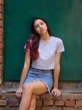 Un retrato de una muchacha hermosa con el pelo oscuro en la ropa casual que presenta en un fondo verde de la puerta Concepto urba Fotos de archivo libres de regalías