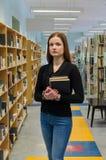 Un retrato de una muchacha que se coloca en la biblioteconomía reserva en sus manos fotografía de archivo