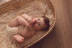 Un retrato de una muchacha de seis meses miente en una cesta de mimbre al lado de la ventana fotografía de archivo
