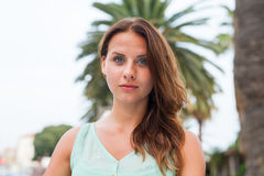 Un retrato de una muchacha, sentándose cerca de la palmera Foto de archivo libre de regalías