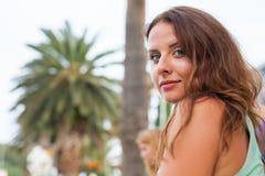 Un retrato de una muchacha, sentándose cerca de la palmera Foto de archivo