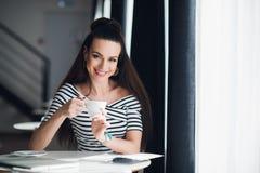 Un retrato de una mujer con una sonrisa perfecta que celebra una taza de café o de capuchino cerca de ventana La señora adulta se Fotos de archivo