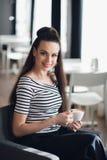 Un retrato de una mujer con una sonrisa perfecta que celebra una taza de café o de capuchino cerca de ventana La señora adulta se Foto de archivo libre de regalías