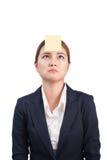 Un retrato de una mujer de negocios confusa joven con una nota pegajosa foto de archivo libre de regalías