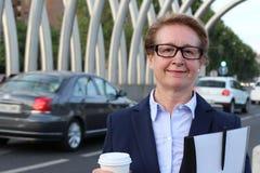 Un retrato de una mujer de negocios de mirada satisfecha con sostenerse a ir taza de café, de carpeta de los documentos y de plum Imagenes de archivo