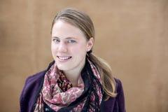 Un retrato de una mujer elegante joven que está sonriendo en la cámara con incluso un fondo marrón Imagen de archivo libre de regalías
