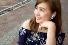 Un retrato de una mujer hermosa está escuchando un podcast Imagen de archivo libre de regalías