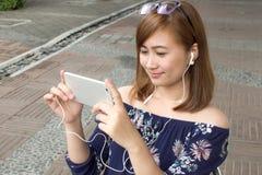 Un retrato de una mujer hermosa está mirando película del teléfono elegante Imagenes de archivo