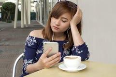 Un retrato de una mujer hermosa está mirando película del teléfono elegante Imagen de archivo libre de regalías