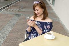 Un retrato de una mujer hermosa está mirando película del teléfono elegante Fotos de archivo libres de regalías