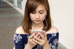 Un retrato de una mujer hermosa está mirando película del teléfono elegante Imagen de archivo