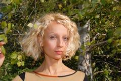 Un retrato de una mujer joven agradable con un pelo rubio rizado y eys azules, colocándose cerca de un abedul y llevando a cabo u Imagenes de archivo