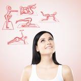 Un retrato de una mujer que está pensando en entrenamientos del crossfit Los iconos aptos de la cruz se dibujan en el fondo rosad Foto de archivo libre de regalías