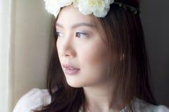 Un retrato de una mujer que lleva una corona de la flor Imagen de archivo libre de regalías