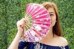 Un retrato de una mujer que sostiene una fan tradicional Imagen de archivo libre de regalías
