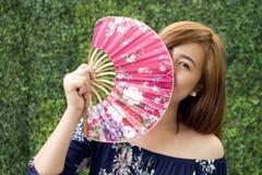 Un retrato de una mujer que sostiene una fan tradicional Fotografía de archivo