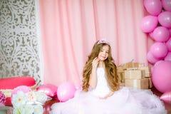 Un retrato de una niña hermosa en un estudio adornó muchos globos del color Imagenes de archivo