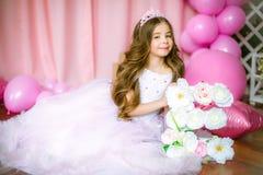 Un retrato de una niña hermosa en un estudio adornó muchos globos del color Foto de archivo libre de regalías