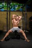 Un retrato de un varón con doblar muscles en un fondo del gimnasio Un culturista con un cuerpo perfecto Hombre de la aptitud trai Fotografía de archivo libre de regalías