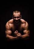 Un retrato de un varón con doblar muscles en un fondo negro Hombre de la aptitud training Un culturista con un cuerpo perfecto Foto de archivo