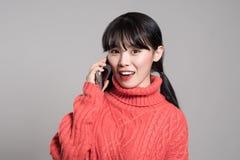 Un retrato del estudio de una mujer asiática de los años 20 que recibe feliz una llamada de teléfono Imágenes de archivo libres de regalías