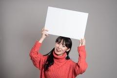Un retrato del estudio de una mujer asiática de los años 20 que sostiene una cartelera con una sonrisa feliz Foto de archivo libre de regalías