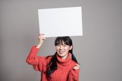 Un retrato del estudio de una mujer asiática de los años 20 que sostiene una cartelera con una sonrisa feliz Imágenes de archivo libres de regalías