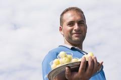 Un retrato del hombre joven que vende el ciruelo dulce en pequeños vidrios Fotografía de archivo