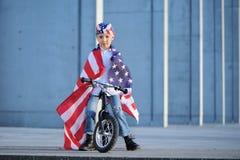 Un retrato del muchacho americano que se sentaba en la bici envolvió la bandera americana Imagenes de archivo