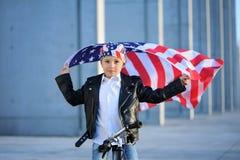 Un retrato del muchacho americano que se sienta en la bici que agita la bandera americana Fotos de archivo