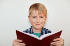 Un retrato del niño pequeño hermoso con el pelo justo y los ojos azules que sostienen un libro en sus manos mientras que se coloc Fotos de archivo libres de regalías