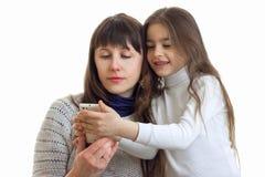 Un retrato del primer de mamáes jovenes e hijas que miran en teléfono Imagen de archivo libre de regalías