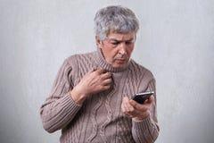 Un retrato del varón mayor con el pelo gris que choca la expresión mientras que mira en su mensaje de la lectura del smartphone U imagenes de archivo